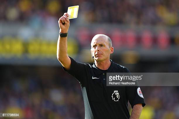 Mike Dean shows a yellow card to a player during the Premier League match between Watford and AFC Bournemouth at Vicarage Road on October 1 2016 in...