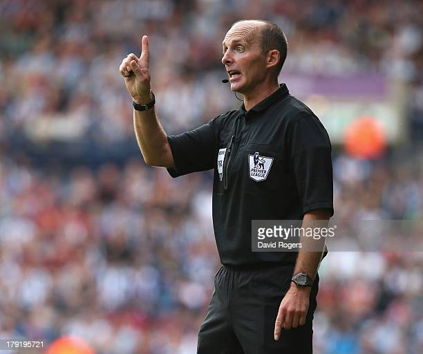 Mike Dean the referee issues instructions during the Barclays Premier League match between West Bromwich Albion and Swansea City at The Hawthorns on...