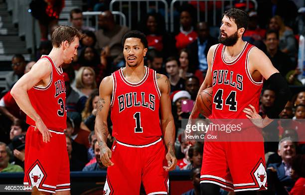 Mike Dunleavy Derrick Rose and Nikola Mirotic of the Chicago Bulls react after a foul during the game against the Atlanta Hawks at Philips Arena on...