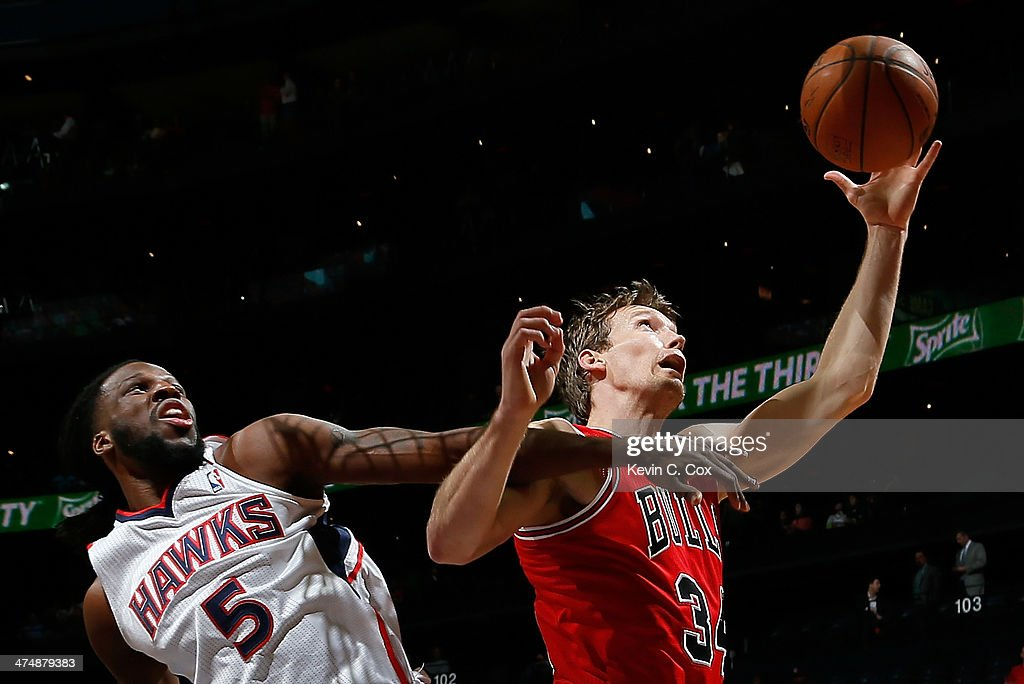 Mike Dunleavy #34 of the Chicago Bulls grabs a rebound against DeMarre Carroll #5 of the Atlanta Hawks at Philips Arena on February 25, 2014 in Atlanta, Georgia.