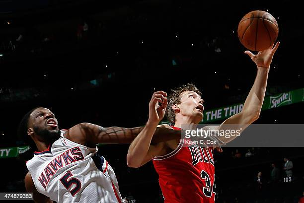 Mike Dunleavy of the Chicago Bulls grabs a rebound against DeMarre Carroll of the Atlanta Hawks at Philips Arena on February 25 2014 in Atlanta...