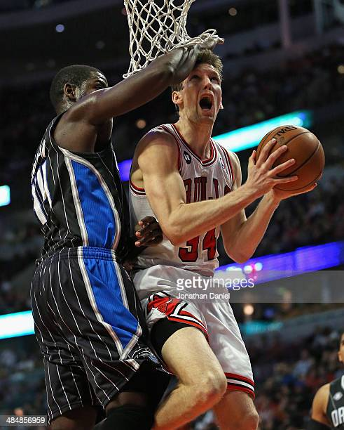 Mike Dunleavy of the Chicago Bulls is fouled by Andrew Nicholson of the Orlando Magic at the United Center on April 14 2014 in Chicago Illinois The...
