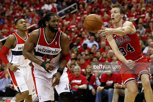 Mike Dunleavy of the Chicago Bulls passes the ball past Nen of the Washington Wizards in fourth quarter action of Game 3 of the Eastern Conference...