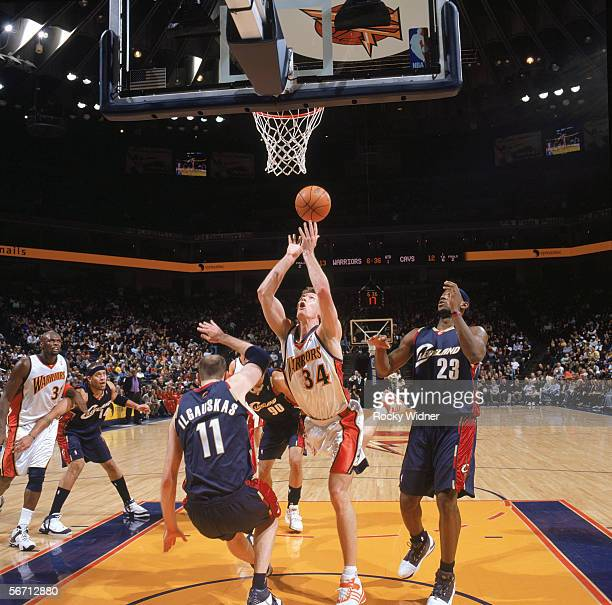 Mike Dunleavy of the Golden State Warriors puts up a shot between Zydrunas Ilgauskas and LeBron James of the Cleveland Cavaliers during a game at The...