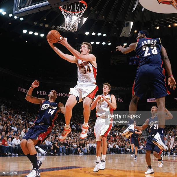 Mike Dunleavy of the Golden State Warriors takes the ball to the basket between Ira Newble and LeBron James of the Cleveland Cavaliers during a game...
