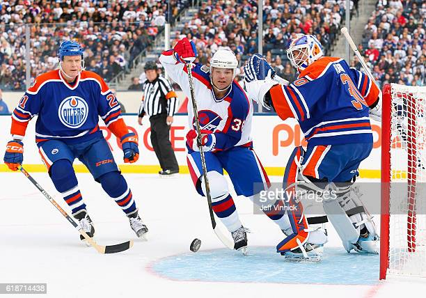 Mike Eagles of the Winnipeg Jets alumni tries to get past Randy Gregg and goaltender Bill Ranford of the Edmonton Oilers alumni during the 2016 Tim...