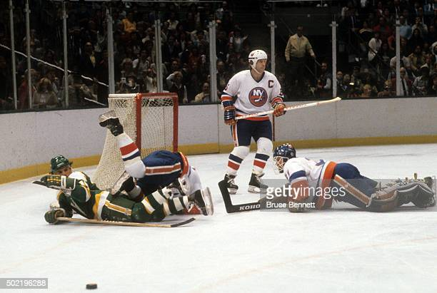 Mike Eaves of the Minnesota North Stars is checked as goalie Billy Smith and Denis Potvin of the New York Islanders defend the net during the 1981...