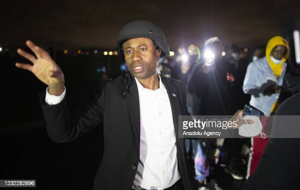 Mike Elliott, the Mayor of Brooklyn Center stands near protesters and signals for police to not shoot rubber bullets at them shortly after he talked...