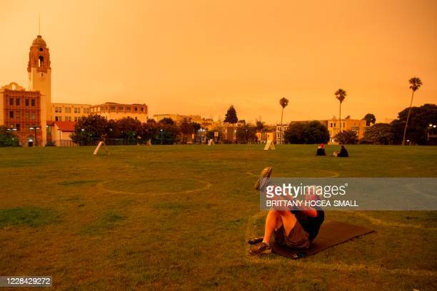 Mike Elliott works out under an orange smoke-filled sky at Dolores Park in San Francisco, California on September 9, 2020. - More than 300,000 acres...