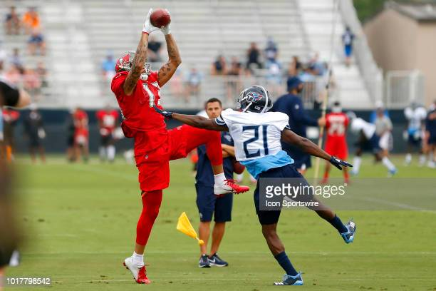 Mike Evans of the Bucs leaps in the air to make a catch over top of Malcolm Butler of the Titans during the joint training camp work out between the...
