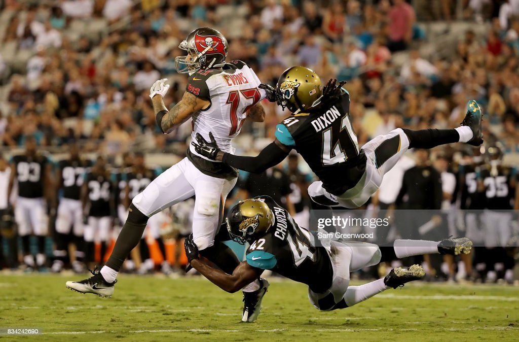 Mike Evans #13 of the Tampa Bay Buccaneers is tackled by Brian Dixon #41 and Barry Church #42 of the Jacksonville Jaguars during a preseason game at EverBank Field on August 17, 2017 in Jacksonville, Florida.