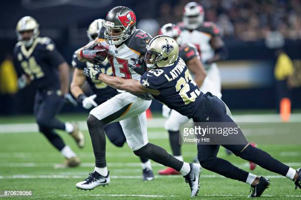 Mike Evans of the Tampa Bay Buccaneers runs the ball and is tackled by Marshon Lattimore of the New Orleans Saints at MercedesBenz Superdome on...