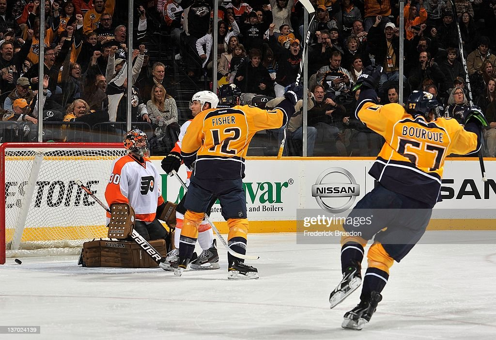 Mike Fisher #12 and Gabriel Bourque #57 of the Nashville Predators celebrate after a Predators goal against Ilya Bryzgalov #30 of the Philadelphia Flyers at Bridgestone Arena on January 14, 2012 in Nashville, Tennessee.