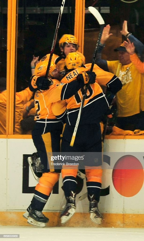 Mike Fisher #12 and James Neal #18 of the Nashville Predators embrace teammate Kevin Fiala #56 after Fiala scored the game-winning goal against the Chicago Blackhawks in overtime in Game Three of the Western Conference First Round during the 2017 NHL Stanley Cup Playoffs at Bridgestone Arena on April 17, 2017 in Nashville, Tennessee.