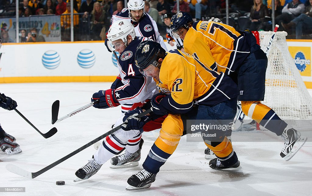 Mike Fisher #12 of the Nashville Predators battles for the puck against John Moore #4 of the Columbus Blue Jackets during an NHL game at the Bridgestone Arena on March 23, 2013 in Nashville, Tennessee.