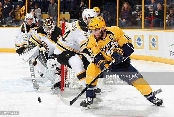 Mike Fisher of the Nashville Predators centers the puck against Zdeno Chara and Zane McIntyre of the Boston Bruins during an NHL game at Bridgestone...