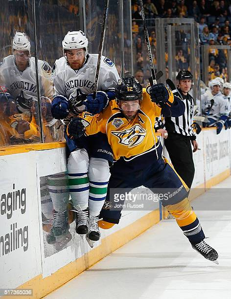 Mike Fisher of the Nashville Predators checks Yannick Weber of the Vancouver Canucks during an NHL game at Bridgestone Arena on March 24 2016 in...