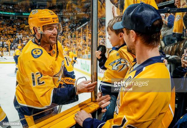 Mike Fisher of the Nashville Predators hands his son Isaiah a puck during warmups prior to Game Two of the Western Conference First Round against the...