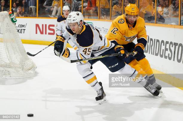 Mike Fisher of the Nashville Predators lifts the stick of Brendan Guhle of the Buffalo Sabres during an NHL game at Bridgestone Arena on March 31...