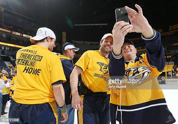 Mike Fisher of the Nashville Predators poses for a selfie with a fan after an overtime win against the Arizona Coyotes during an NHL game at...