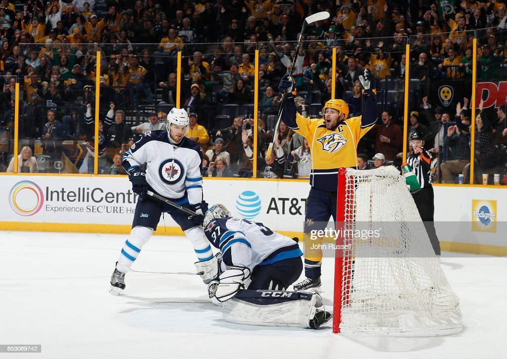 Mike Fisher #12 of the Nashville Predators reacts to the game winning goal by James Neal #18 (not pictured) against Connor Hellebuyck #37 and Ben Chiarot #7 of the Winnipeg Jets during an NHL game at Bridgestone Arena on March 13, 2017 in Nashville, Tennessee.