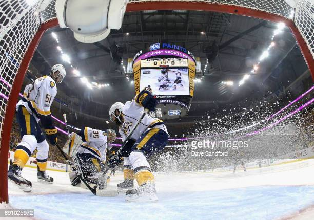 Mike Fisher of the Nashville Predators sprays ice as he helps defend the net with teammates Austin Watson and goaltender Pekka Rinne during the first...