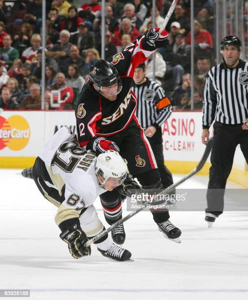 Mike Fisher of the Ottawa Senators bowls over Sidney Crosby of the Pittsburgh Penguins at Scotiabank Place on December 6, 2008 in Ottawa, Ontario,...