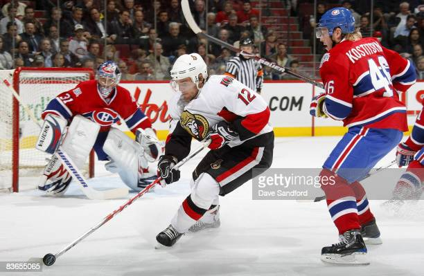 Mike Fisher of the Ottawa Senators carries the puck as he is defended by Andrei Kostitsyn of the Montreal Canadiens during their NHL game at the Bell...