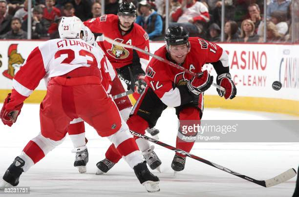 Mike Fisher of the Ottawa Senators chips the puck past Brad Stuart of the Detroit Red Wings at Scotiabank Place on October 11 2008 in Ottawa Ontario...