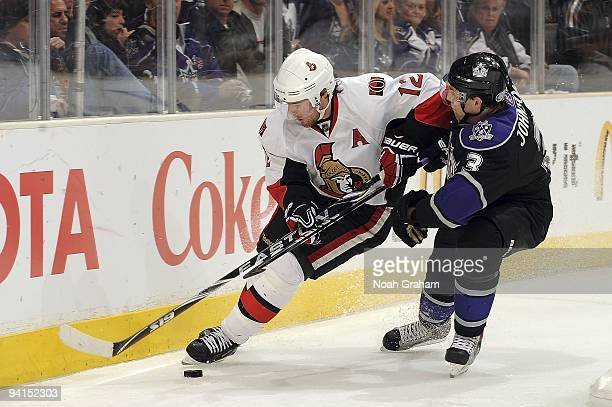 Mike Fisher of the Ottawa Senators controls the puck alongside the boards against Jack Johnson of the Los Angeles Kings during the game on December...