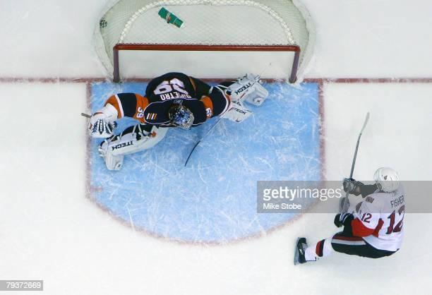 Mike Fisher of the Ottawa Senators scores on goaltender Rick DiPietro of the New York Islanders in the third period on January 29, 2008 at Nassau...