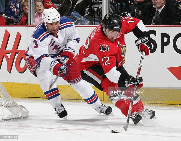Mike Fisher of the Ottawa Senators stickhandles the puck against pressure from Michal Rozsival of the New York Rangers at Scotiabank Place on January...