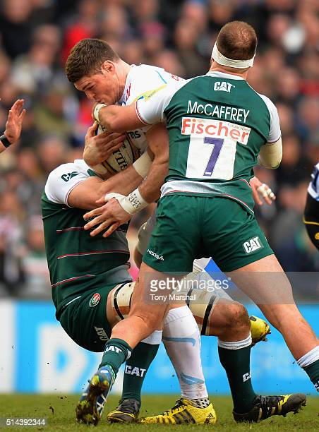 Mike Fitzgerald and Lachlan McCaffrey of Leicester Tigers tackle Dave Ewers of Exeter Chiefs during the Aviva Premiership match between Leicester...