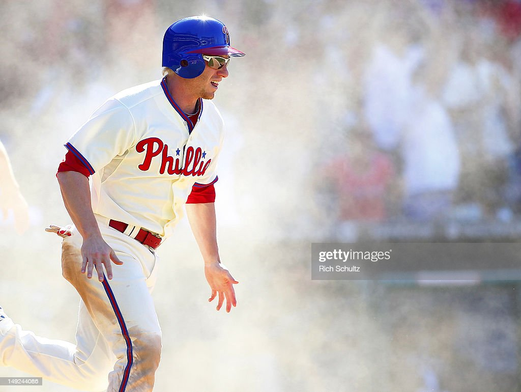 Mike Fontenot #18 of the Philadelphia Phillies reacts in a cloud of dust after scoring the game winning run on a single by teammate Jimmy Rollins #11 (not pictured) in the 10th inning off closer Francisco Rodriguez #57 of the Milwaukee Brewers during a MLB baseball game on July 25, 2012 at Citizens Bank Park in Philadelphia, Pennsylvania. The Phillies defeated the Brewers 7-6.