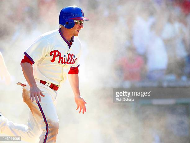 Mike Fontenot of the Philadelphia Phillies reacts in a cloud of dust after scoring the game winning run on a single by teammate Jimmy Rollins in the...