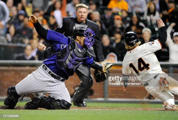 Mike Fontenot of the San Francisco Giants beats the throw to the plate avoiding the tag of Wilin Rosario of the Colorado Rockies in the eighth inning...