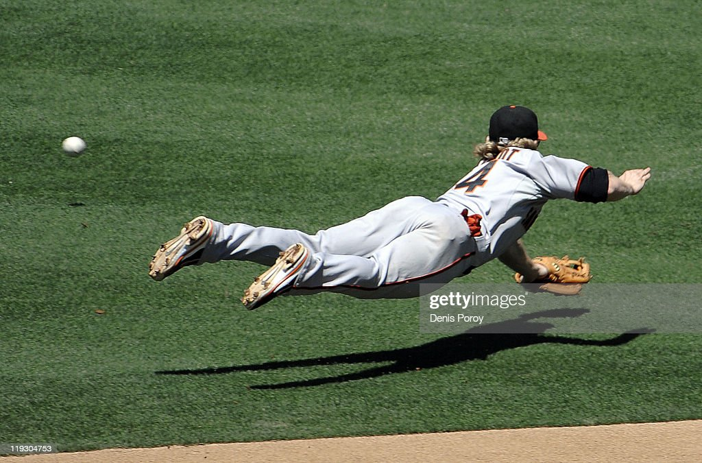 Mike Fontenot #14 of the San Francisco Giants dives for a single hit by Orlando Hudson #1 of the San Diego Padres during the fourth inning of a baseball game at Petco Park on July 17, 2011 in San Diego, California.