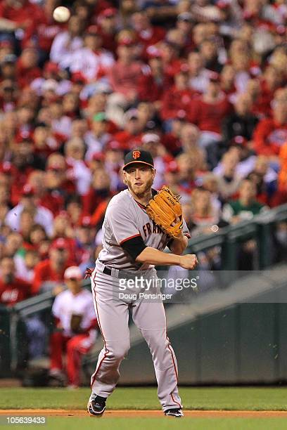 Mike Fontenot of the San Francisco Giants throws an errant throw to first base on a ball hit by Placido Polanco of the Philadelphia Phillies leading...