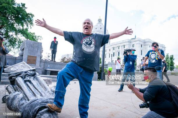 Mike Forcia of the Black River Anishinabe celebrated after the Christopher Columbus statue was toppled in front of the Minnesota State Capitol in St...