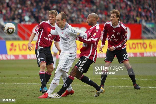 Mike Frantz of Nuernberg and Mickael Tavares of Nuernberg challenge Arjen Robben of Bayern during the Bundesliga match between 1 FC Nuernberg and FC...