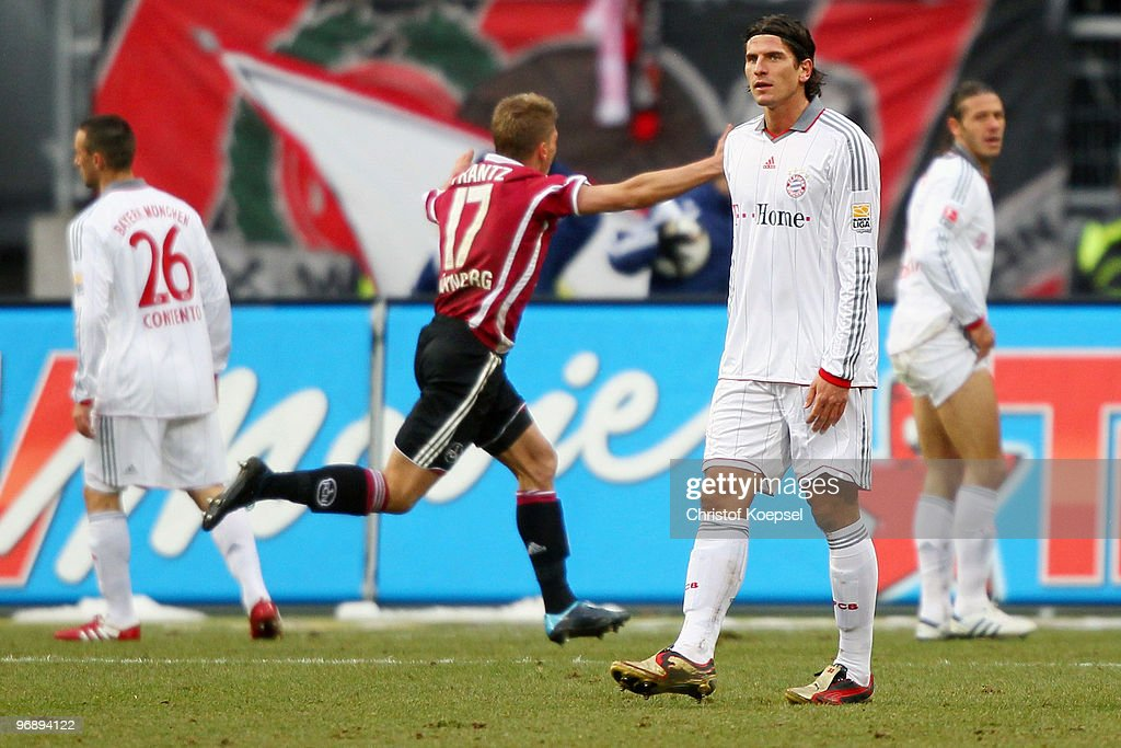 Mike Frantz of Nuernberg (C) celebrates his team's first goal and Diego Contento (L), Mario Gomez and Martin Demichelis of Bayern look dejected during the Bundesliga match between 1. FC Nuernberg and FC Bayern Muenchen at Easy Credit Stadium on February 20, 2010 in Nuremberg, Germany.
