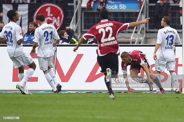 Mike Frantz of Nuernberg celebrates scoring the first team goal whilst Lukas Schmitz of Schalke looks on with his team mates Christoph Metzelder and...