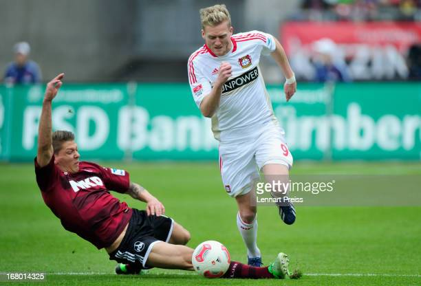 Mike Frantz of Nuernberg challenges Andre Schuerrle of Leverkusen during the Bundesliga match between 1 FC Nuernberg and Bayer 04 Leverkusen at...