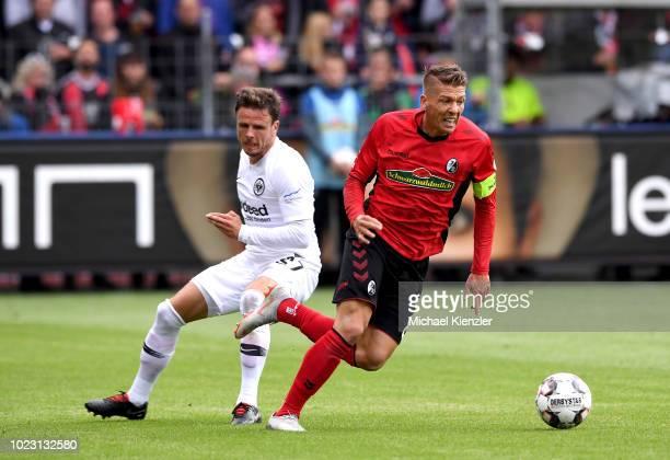 Mike Frantz of SC Freiburg challenges Nicolai Mueller of Eintracht Frankfurt during the Bundesliga match between Sport Club Freiburg and Eintracht...