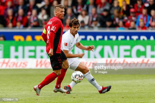 Mike Frantz of SportClub Freiburg and Lucas Torro of Eintracht Frankfurt battle for the ball during the Bundesliga match between SportClub Freiburg...