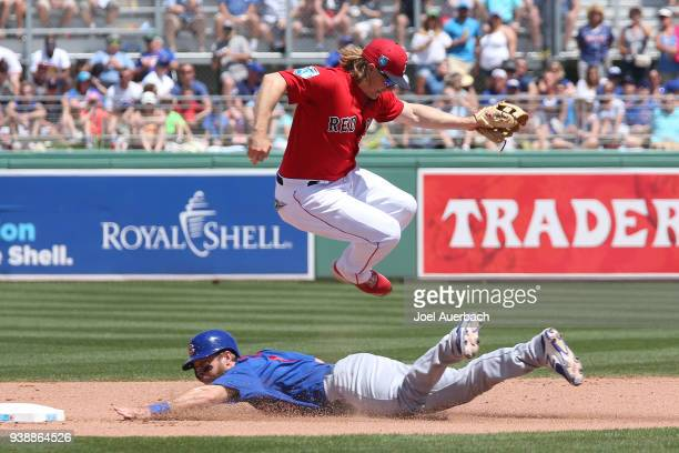 Mike Freeman of the Chicago Cubs steals second base before Brock Holt of the Boston Red Sox can tag him during the fourth inning of a spring training...