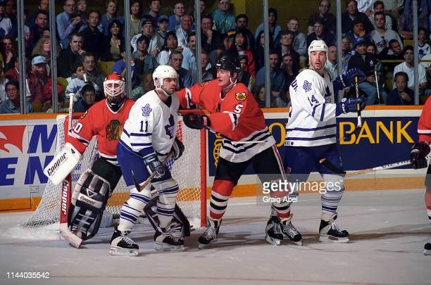 Mike Gartner and Dave Andreychuk of the Toronto Maple Leafs skate against Ed Belfour and Steve Smith of the Chicago Black Hawks during NHL playoff...