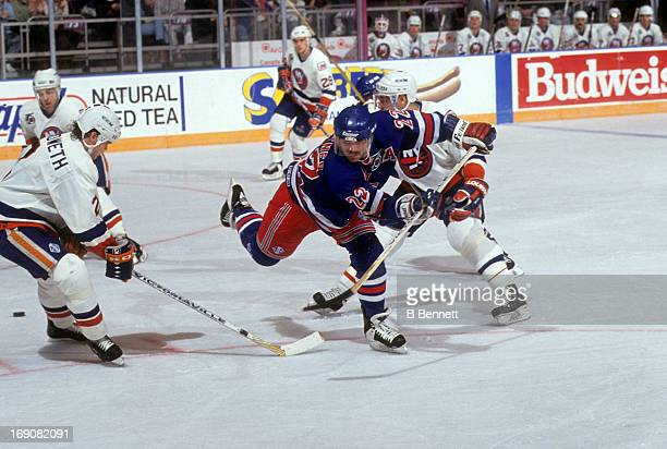 Mike Gartner of the New York Rangers has the puck poke checked away by Dean Chynoweth of the New York Islanders on February 14 1992 at the Madison...