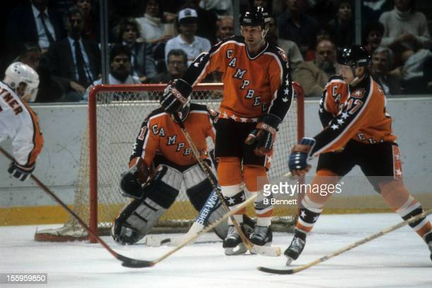 Mike Gartner of the Wales Conference and the Washington Capitals shoots the puck as Paul Coffey and Jari Kurri of the Campbell Conference and the...