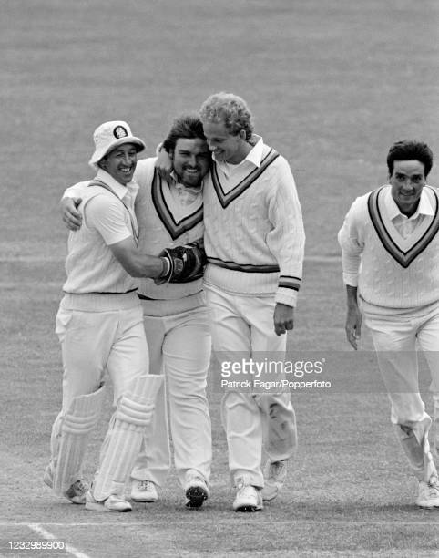 Mike Gatting of England is congratulated by teammates Bob Taylor and David Gower after taking his first Test wicket, New Zealand batsman Martin Crowe...